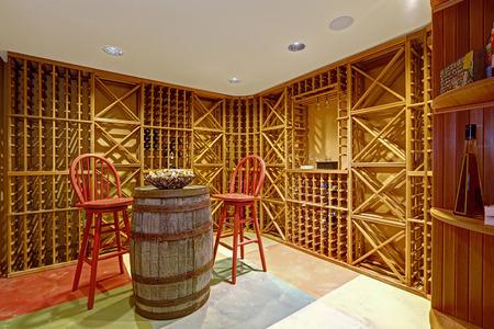 Weinkeller Innen in Kellerraum mit dekorativen Holzfass und zwei rote Hochstühle Standard-Bild
