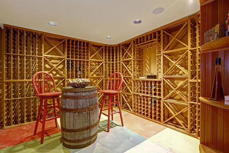 Wine cellar interior in basement room with decorative wooden barrel and two red high chairs Reklamní fotografie