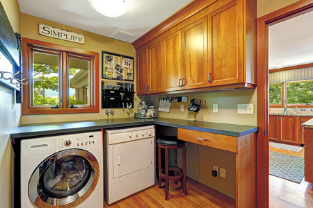 laundry room: Small craft room with wooden storage combintaion and laundry appliances