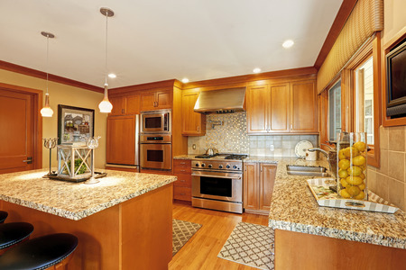 granite kitchen: Beautiful kitchen storage combination with granite tops and modern steel stainless appliances Stock Photo