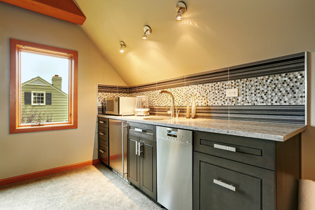 back kitchen: Dark green kitchen cabinets with back splash trim, steel appliances in small room with vaulted ceiling Stock Photo