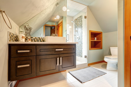 vaulted door: Brown vaniry cabinet with mirror, glass door shower in small bathroom with vaulted ceiling Stock Photo