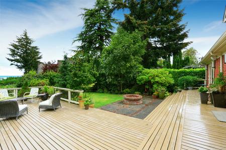 Staking dek met patio en een achtertuin met een baksteen vuurplaats Stockfoto - 32041916