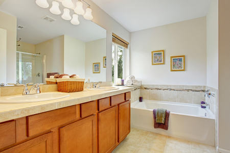 Bathroom with honey tone vanity cabinet and large mirror. Cabinet decorated with wicker basket for towels photo