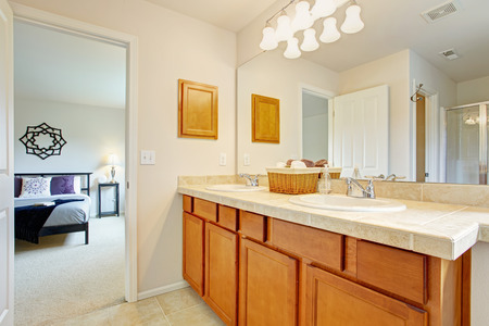 master bath: Bathroom with honey tone vanity cabinet and large mirror. Exit to master bedroom