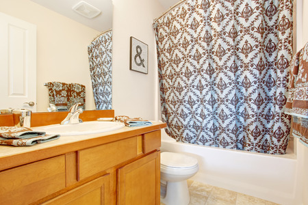 honey tone: Bathroom with honey tone vanity cabinet and mirror. Decorated with towels and curtain