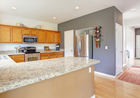 honey tone: Kitchen room interior with granite top, steel stainless appliances and honey tone storage combination Stock Photo