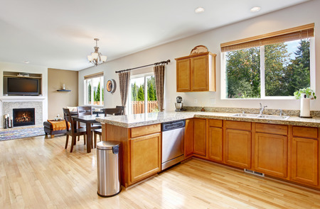 honey tone: Kitchen room interior with granite top, steel appliances and honey tone storage combination. View of dining area with exit to backyard and cozy living room with fireplace and tv