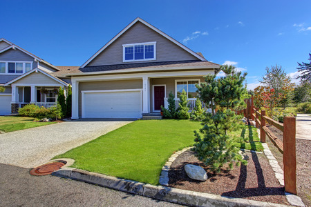 House exterior with garage and driveway. Beautiful front yard landscape during summer in Washington state Stockfoto