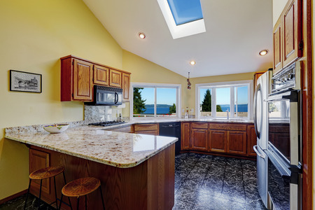 black appliances: Beautiful kitchen room with high vaulted ceiling and  skylight, black granite tile floor. Room has amazing bay view