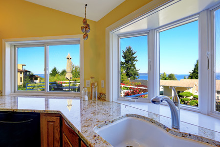 Kitchen cabinet with granite tops and sink with steel faucet. Kitchen has beautiful window view.