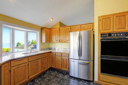 Kitchen room with black granite tile floor and granite tops. Steel refrigerator and black built-in oven photo