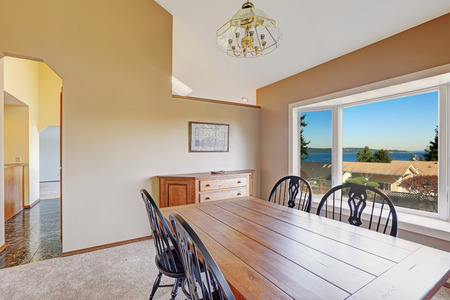 dining table and chairs: Cozy dining area with scenic window view. Wooden table with rusctic black chairs and wooden cabinet