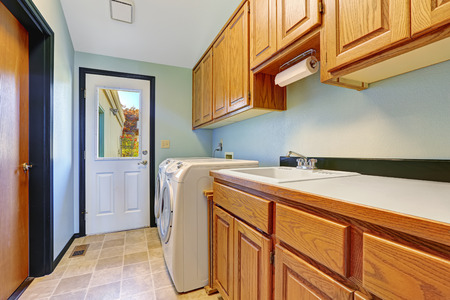 laundry room: Laudry room with cabinets and white laundry appliances. Room has exit to backyard Stock Photo