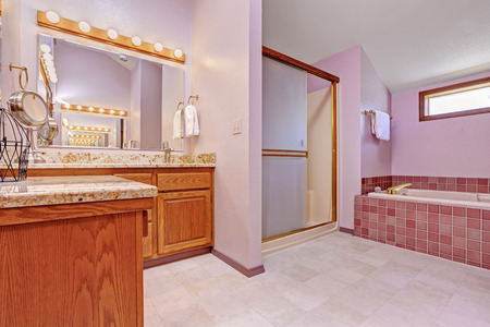 Bathroom interior in light pink tone with tile trim, shower, bath tub and bathroom vanity cabinet photo