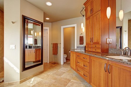 master bath: Spacious luxury bathroom with wooden storage combination and granite tops. Stock Photo