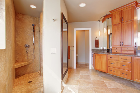 master bath: Spacious luxury bathroom with wooden storage combination, toilet and open shower with tile trim