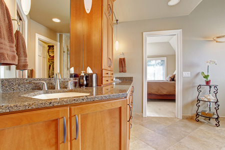 master bath: Spacious luxury bathroom in master bedrooom. Wooden storage combination with  granite tops and mirror