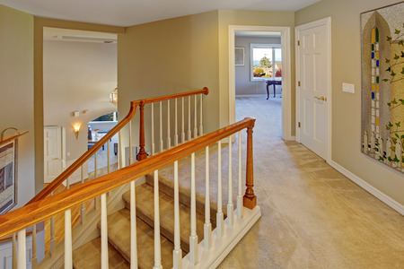 upstairs: Upstairs hallway with staircase. Staircase with carpet steps, white railings with brown trim Stock Photo