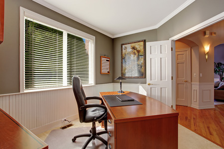 Luxury office room with wooden desk, leather whirlpool chair. Grey walls with white plank trim photo
