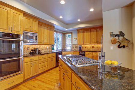 Spacious kitchen room with maple storage combination, kitchen island and built-in stove photo