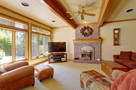 Living room with wide windows, brick fireplace and ceiling beams photo