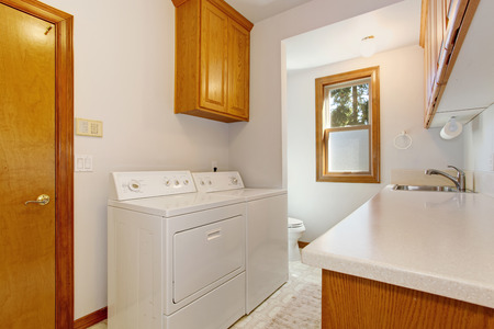 laundry room: White laundry room with maple cabinets