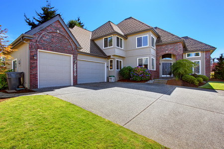 front view: Luxury house with tile roof and brick trim. View of garage with driveway Stock Photo