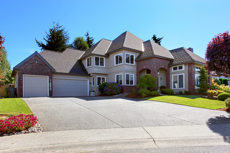 Big luxury house with tile roof and brick trim. View of garage with driveway. Beautiful front yard landscape photo