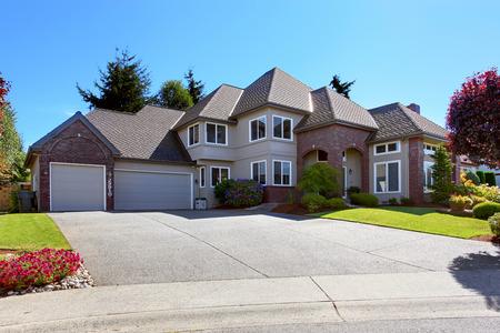 casa blanca: Casa de lujo grande con techo de tejas y adornos de ladrillo. Vista del garaje con entrada para coche. Hermoso paisaje patio delantero