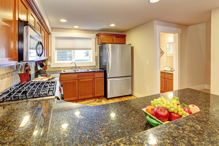 kitchen cabinets: Maple kitchen cabinets with steel appliances and granite tops.