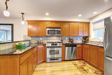 kitchen cabinets: Maple kitchen cabinets with steel appliances and granite tops. Practical design with tile back splash trim Stock Photo