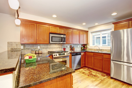 Maple kitchen cabinets with steel appliances and granite tops. Practical design with tile back splash trim photo