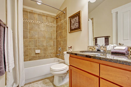bathroom wall: Bathroom interior. Maple cabinet with granite top and mirror. White bath tub with tile wall trim and white curtain