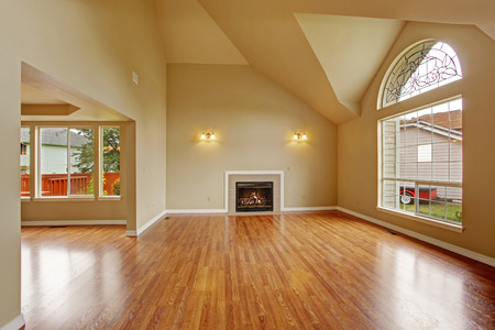 Spacious living room with high ceiling, big arch window, fireplace and new hardwood floor in empty new house photo