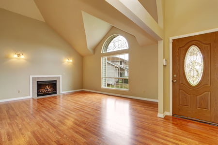 remodeled: Spacious living room with high ceiling, big arch window, fireplace and new hardwood floor in empty new house.