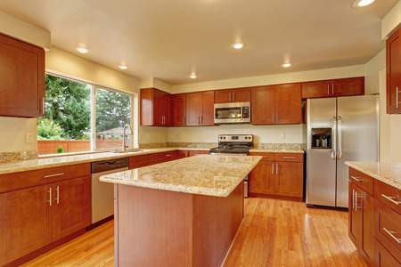 Kitchen with bright wooden cabinets, steel appliances and granite tops. Kitchen room has kitchen island