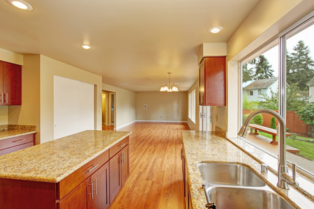 Kitchen with bright wooden cabinets and granite tops. Kitchen room has kitchen island. Empty living room photo