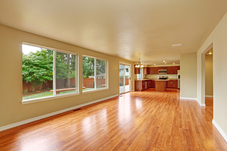 Empty house interior with new hardwood floor. Spacious empty living room with exit to backayrd area and kitchen area
