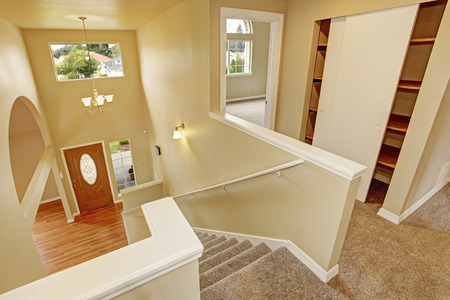 upstairs: Upstairs hallway with staircase with panoramic view on entrance hallway with archway