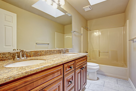 skylights: Bathroom cabinet with two sinks, granite top and large mirror in bright bathroom with skylight
