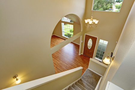 Panoramic view of entrance hallway with hardwood floor and archway. View  from staircase photo