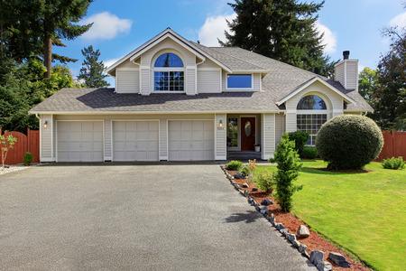 Luxe huis buitenkant met pannendak. Huis met drie auto garage en voortuin landschap