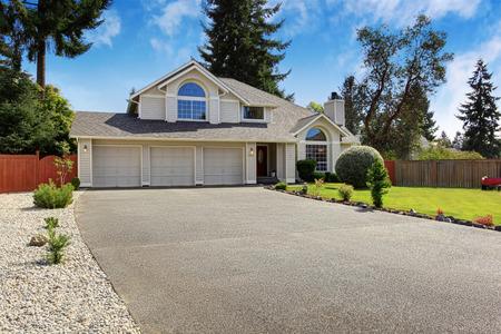 瓦の屋根を持つ高級ハウス外観。3 つの駐車ガレージと庭風景の家