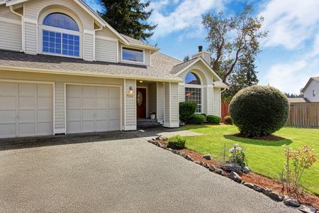 Casa de lujo exterior con techo de tejas. Casa con garaje y paisaje patio delantero