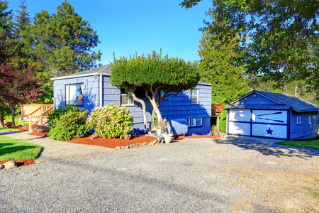garage on house: Light blue  house with garage and front yard Stock Photo