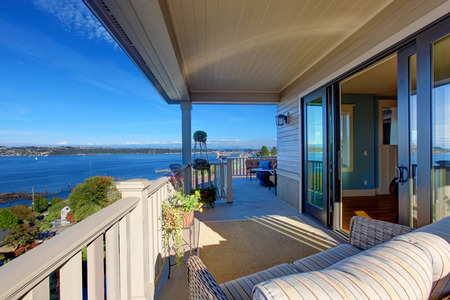 House with wraparound walkout deck. Sitting area with wicker chair. View of puget sound Tacoma, WA photo
