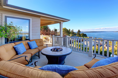 Cozy patio area with comfort settees and fire pit. Deck with Puget Sound view. Tacoma, WA Stock Photo