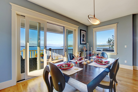 dining table and chairs: Light blue dining area with sliding glass door to walkout deck. Served wooden table with chairs Stock Photo