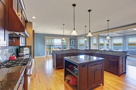 kitchen island: Luxury kitchen with dark brown storage combination, kitchen island and tile back splash trim. Kitchen has  sliding doors to walkout deck Stock Photo